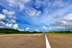 机场有空白线路、绿色山和蓝天的跑道出租汽车 图库摄影