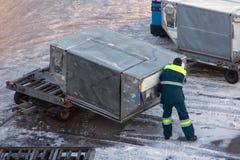 机场的职员操作货箱 免版税库存图片