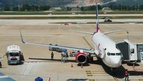 机场雇员在飞行前加油飞机 乘客赢得他们的在客舱的席位 乘客行李是 股票视频