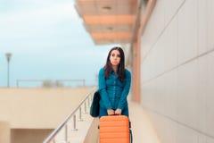 机场驻地的不快乐的疲乏的妇女带着手提箱 图库摄影