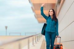 机场驻地的愉快的妇女带着手提箱 免版税库存照片