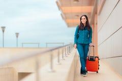 机场驻地的愉快的妇女带着手提箱 库存照片