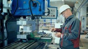 机械在cnc铣床中心前的技术员测量的切割工具在工具车间 影视素材