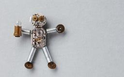 机械嵌齿轮转动字符由钟表机构齿轮和元素做成 有轻的电灯泡的滑稽的抽象玩具在灰色 免版税库存照片