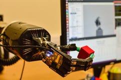 机械机器人手在研究实验室拿着一个红色立方体 免版税库存照片