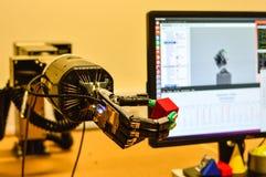 机械机器人手在研究实验室拿着一个红色立方体 免版税库存图片