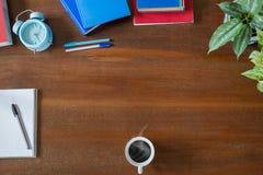 杂乱书、课本、笔、绿色植物、笔记本、热的咖啡杯和蓝色经典闹钟在葡萄酒难看的东西木桌上 免版税库存图片
