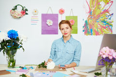 杂乱书桌的确信的花卉设计师 免版税库存照片
