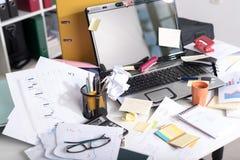 杂乱和凌乱的书桌 免版税库存图片