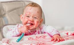 杂乱和肮脏的婴孩从匙子吃着 库存照片