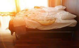 杂乱床在一间温暖的卧室阳光天的早晨 库存图片