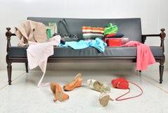 杂乱衣裳、夫人袋子和鞋子在沙发驱散了 库存图片