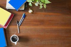 杂乱课本、笔记本、文件、笔、绿色植物,怀表和热的加奶咖啡杯子在葡萄酒难看的东西木背景 库存照片