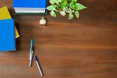 杂乱课本、笔记本、文件、笔、绿色植物,怀表和热的加奶咖啡杯子在葡萄酒难看的东西木背景 免版税图库摄影