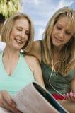 读杂志的两名妇女户外。 免版税库存图片