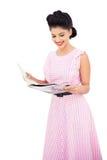 读杂志的微笑的黑发模型 免版税库存图片