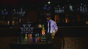 杂技展示由玩杂耍两个瓶和烧杯混合的男服务员执行了 酒吧背景 慢的行动 股票录像