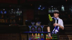 杂技展示由玩杂耍两个瓶和烧杯混合的男服务员执行了 酒吧背景 影视素材