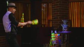 杂技展示由玩杂耍两个瓶和烧杯混合的男服务员执行了 酒吧背景 股票录像