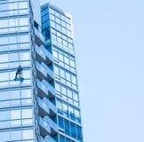 杂物工,当清洗大厦的窗口外面时 免版税库存照片