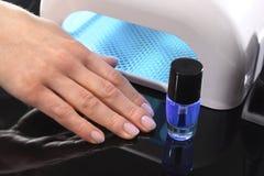 杂种修指甲,紫外灯,钉子板材治疗 图库摄影