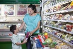 杂货的母亲和儿子购物在超级市场,北京 免版税库存照片