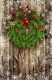 从杉木枝杈和红色球的圣诞节花圈在木头 免版税库存图片