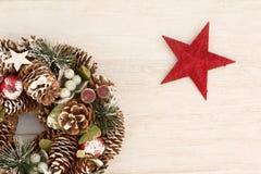 杉木锥体和一个红色星精美圣诞节花圈  免版税图库摄影