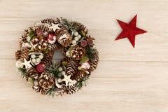 杉木锥体和一个红色星精美圣诞节花圈  免版税库存图片