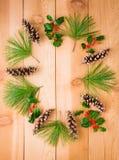 杉木锥体和分支用霍莉莓果在圈子框架在wo 免版税图库摄影