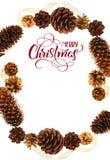 杉木锥体和文本圣诞快乐框架  书法字法 库存照片