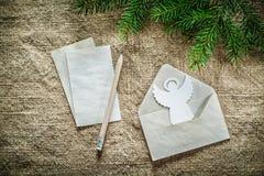 杉树分支信封信件在袋装的backgro的铅笔天使 库存照片