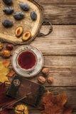 李子、坚果和叶子有葡萄酒笔记本的和茶与影片过滤器影响顶视图 免版税库存图片