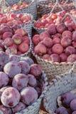 李子和苹果在篮子在市场上 库存图片