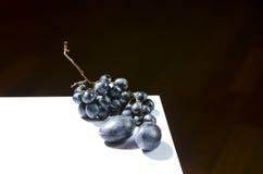 李子和葡萄在桌上 库存照片