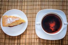 李子在一个杯子的松糕在秸杆卧具的热的茶 图库摄影