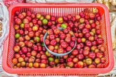 李子在塑料篮子在泰国新鲜市场上 免版税库存照片