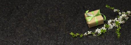 李子开花在古色古香的布朗花岗岩counte的分支和礼物盒 库存照片