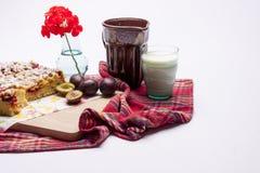 李子蛋糕和杯子在白色的牛奶。 免版税库存照片
