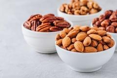 杏仁、胡桃、核桃和榛子在白色碗在灰色背景 坚果混合 健康食物和快餐 免版税库存图片