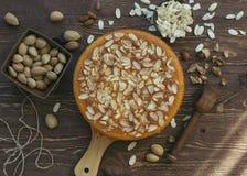 杏仁蛋糕在木板材和服务用可口被轰击的杏仁 装饰了用新鲜的未加工的杏仁 免版税库存图片