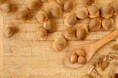 杏子坑和仁顶视图在一把土气木被抓的委员会和匙子有拷贝空间的 健康背景的食物 库存图片