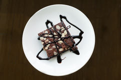杏仁在一块白色板材的果仁巧克力蛋糕 库存图片