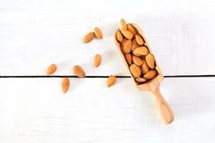 杏仁坚果充分的木瓢在白色木背景的 免版税库存照片