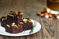 杏仁黑暗的果仁巧克力用在白色板材的咖啡在木桌ba 库存图片