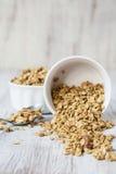 杏仁从白色碗溢出的早餐谷物格兰诺拉麦片 免版税库存图片