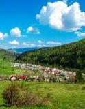村庄向峡谷,用绿色木头盖的山 免版税图库摄影
