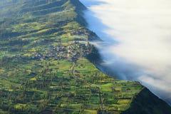 村庄和峭壁在Bromo火山山 免版税库存图片