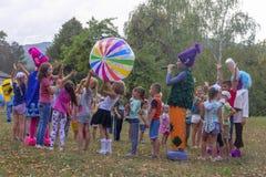村庄和竞争的假日天有设计卡通者和儿童的游乐场的在公园在秋天 免版税库存图片