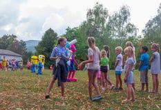 村庄和竞争的假日天有设计卡通者和儿童的游乐场的在秋天的公园 库存照片